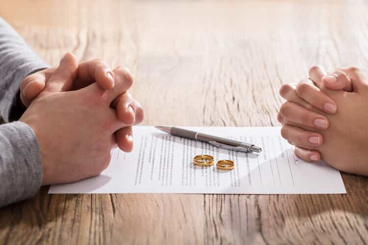 the folded hands of a husband and wife sit on top of DIY divorce papers with their gold wedding rings and a pen